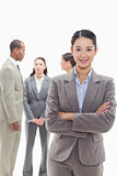 Businesswoman smiling and crossing her arms with co-workers