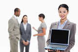 Businesswoman smiling showing a laptop screen with co-workers in