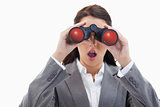 Close-up of a surprised businesswoman looking through binoculars