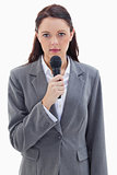 Close-up of a serious businesswoman holding a microphone