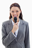 Businesswoman smiling and holding a microphone