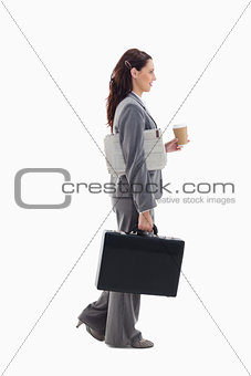 Profile of a businesswoman walking with a briefcase, newspaper a