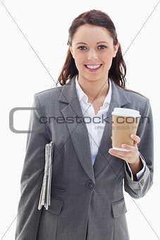 Businesswoman smiling with a newspaper and coffee
