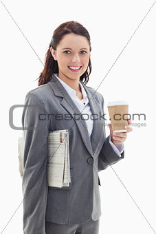 Businesswoman smiling with a newspaper and a coffee