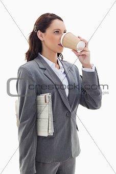 Businesswoman with a newspaper drinking a coffee
