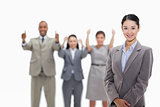 Businesswoman smiling with co-workers approving in the backgroun