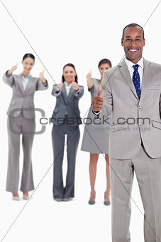 Business team smiling with thumbs up