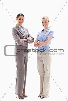 Two smiling women crossing their arms