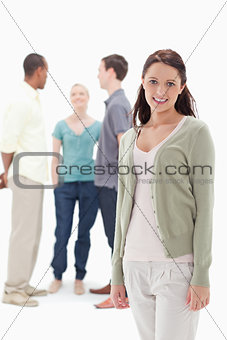 Woman smiling with her friends chatting behind