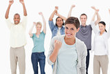 Woman clenching her fist with people behind raising their arms