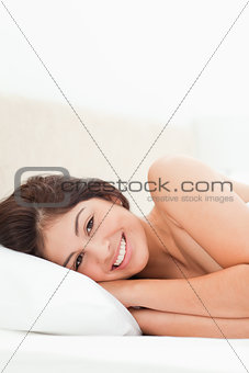 A woman lying on a bed, her head turned to the side, her eyes ar