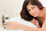 Woman is lying on a bed with a clock in her hand and is looking 