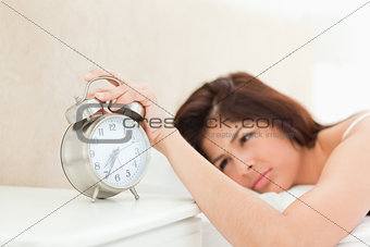 An alarm clock showing the time, being silenced by a woman lying