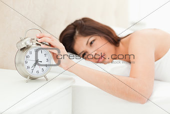 A woman lying in her bed with her hand on the alarm clock, which