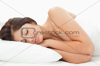 A woman lying on the bed with her head on the pillow and her han