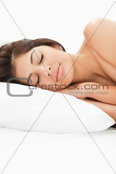 A woman sleeping on the bed with her head resting on the pillow,