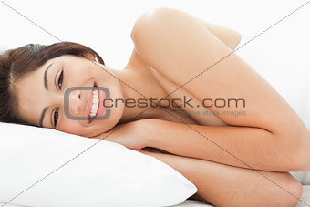 A woman is lying on the bed, her head is resting on the pillow w