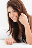 Close up of woman smiling with a hand in her hair while lying on