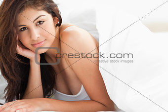 Woman under a quilt looking forward with a hand placed against h