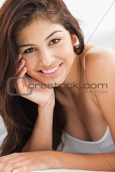 Close up of woman with a hand against her cheek, smiling and loo