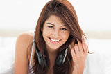 Woman looking straight ahead while smiling and clasping her hair