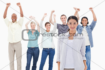 Close-up of a woman with people raising their arms