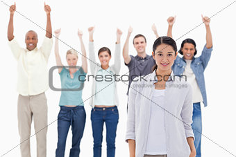 Close-up of a girl with people raising their arms with their thu