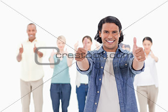 Close-up of a man smiling with his thumbs-up with people behind