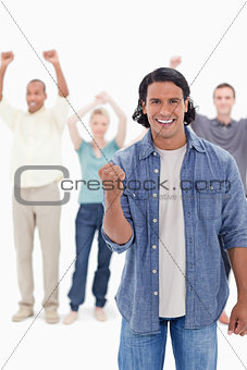Big close-up of a man clenching his hand with people raising the