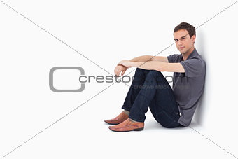 Man sitting against a wall