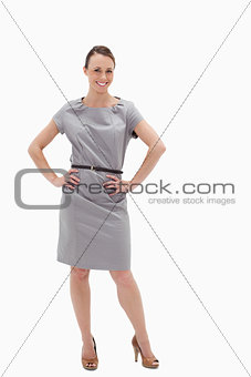 Smiling woman posing in a dress with her hands on her hips