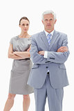 Serious white hair businessman with a woman behind him crossing