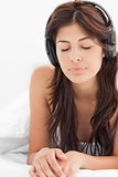 Close up, woman listening to her headphones with her eyes closed