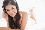 Woman with crossed legs smiling while listening to her headphone
