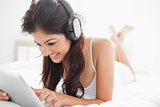 Woman with her legs crossed on the bed listening to headphones,