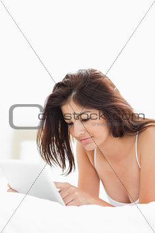 Woman using a tablet while lying on the bed