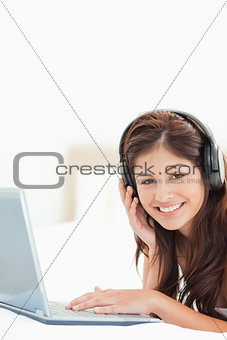 Close up, woman using headphones and laptop on a bed
