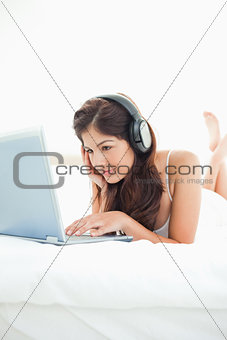 Woman listening to her headphones and watching her laptop, with