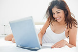 Woman lying across her bed, using her laptop and enjoying what s