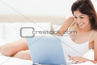 Woman on her laptop smiling as she watches her programme while s