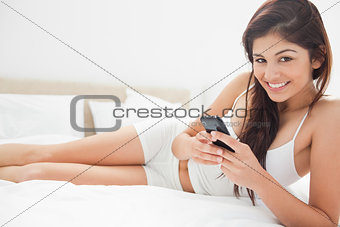 Woman lying on her bed smiling as she uses her smartphone