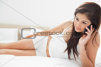 Woman lying on her bed as she makes a phone call on her smartpho