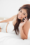 Close up, woman smiling and making a phone call from her bedroom