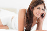 Woman relaxing on her bed making a phonecall as she lies forward