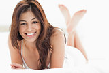 Woman lying down, smiling with her legs crossed and raised up 