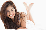 Woman lying down with her legs crossed and raised, smiling with