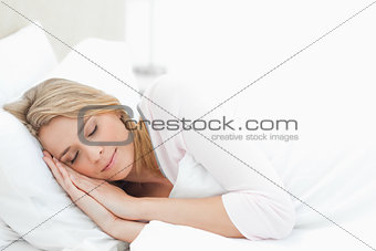 Woman resting in bed, with hands by her head