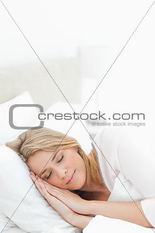 Vertical shot, woman sleeping in bed, with hands and head restin