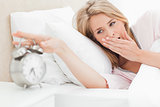 Woman yawning while she reaches out to silence her alarm clock
