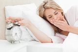 Woman with her eyes closed is reaching to silence her alarm cloc